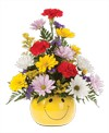 A cheery smiley face container holds a one sided arrangement with carnations, daisy poms, purple statice, and solidago.16in H x 12in W